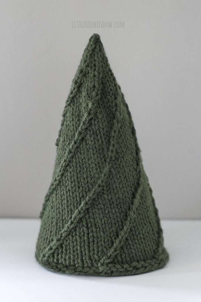 The Medium Cozy Christmas tree is knit in dark green worsted weight yarn with simple lines of twisted stitches.