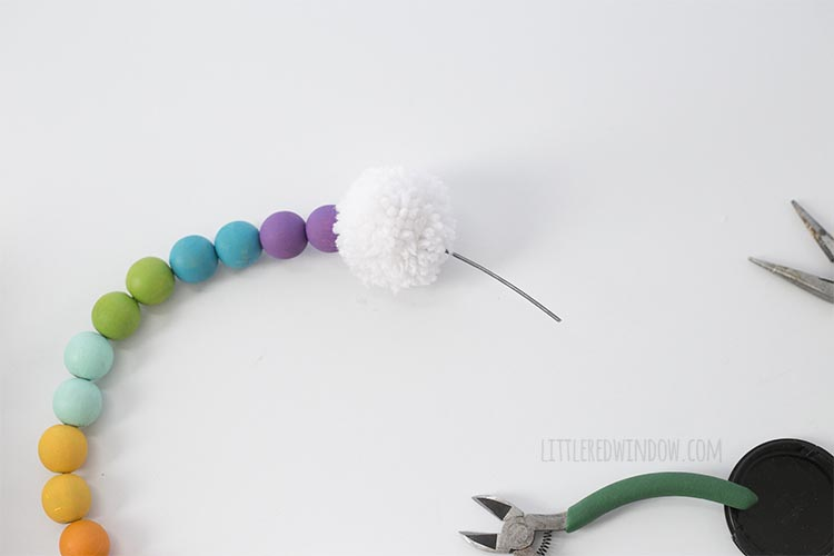 Add a pom pom to the end of your DIY rainbow wall hanging!