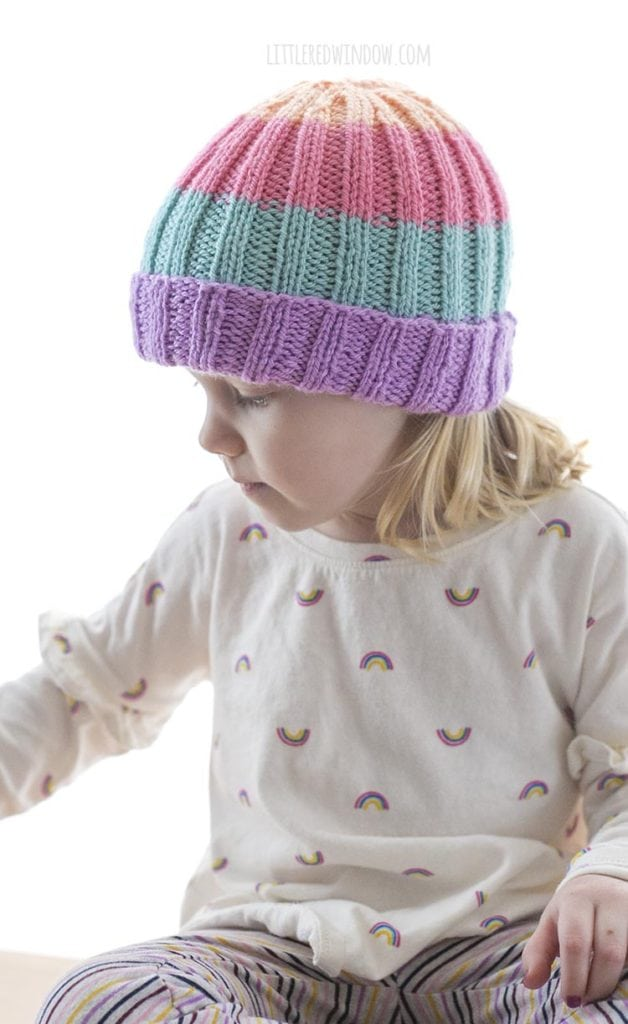 Little girl wearing sherbet hat and looking to the side