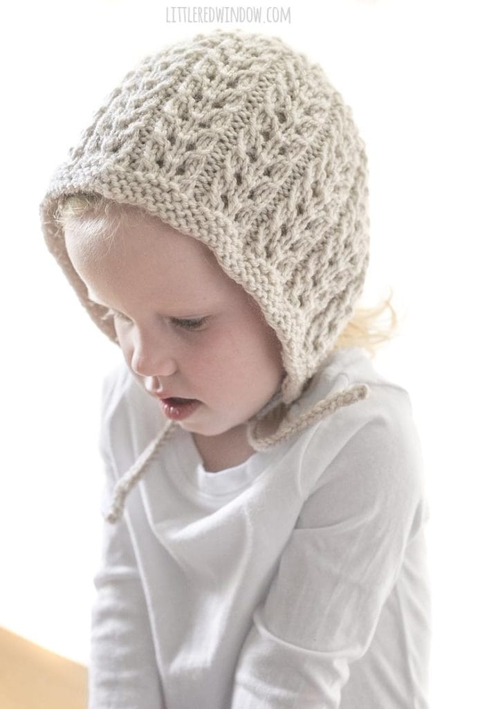 toddler girl wearing tan lace bonnet and looking down