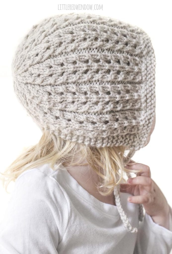 This easy ribbed lace knitting stitch makes the Flutter Lace Baby Bonnet knitting pattern so special and unique picture of a girl wearing bonnet looking off to the right