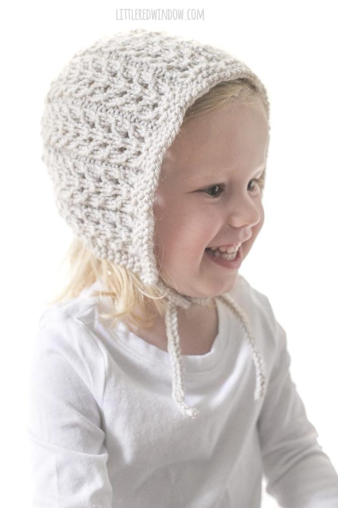smiling toddler wearing tan colored flutter lace bonnet