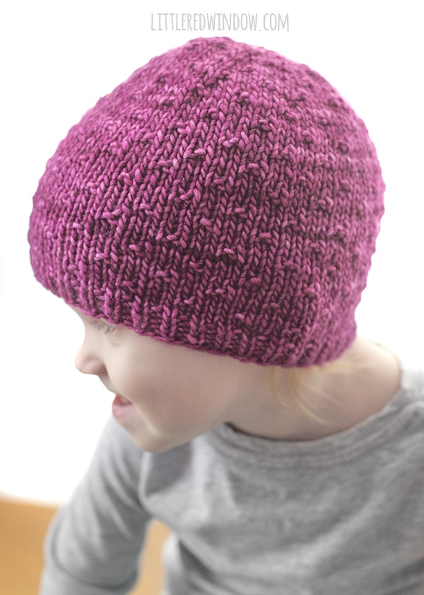 girl looking to the left and wearing pink knit dot hat