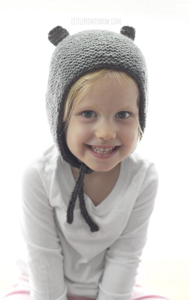 Smiling little girl wearing a gray knit bonnet with bear ears