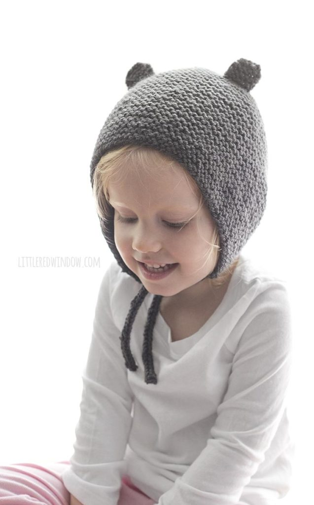 little girl looking down and wearing gray knit bonnet with bear ears