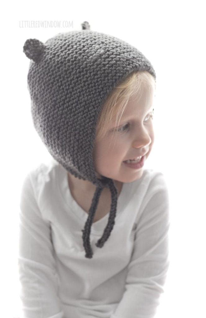 little girl wearing bear ear knit bonet and looking off to the right