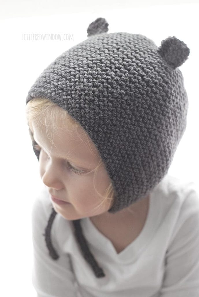little girl wearing gray bear ear knit bonnet and looking off to the left