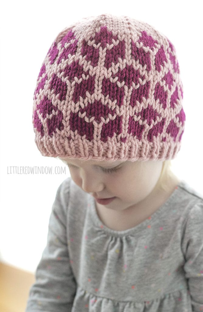 little girl wearing knit hat with tumbling blocks and looking down and to the left