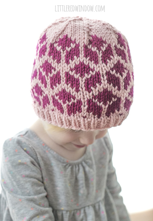 little girl wearing knit hat with tumbling blocks and looking down and to the right