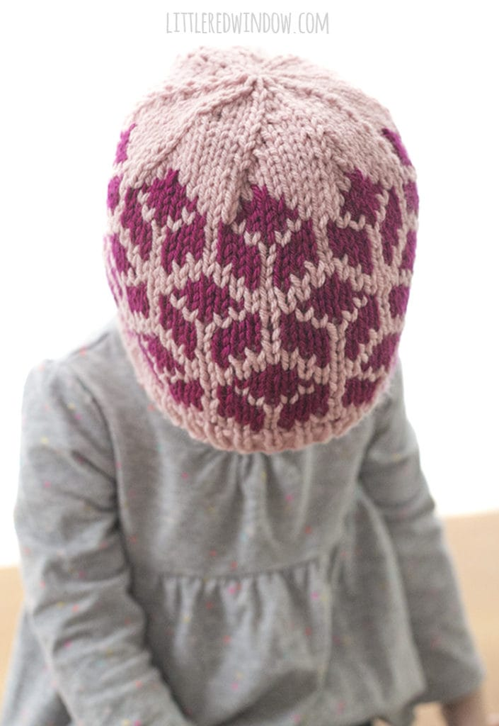 little girl wearing knit hat with tumbling blocks and looking down