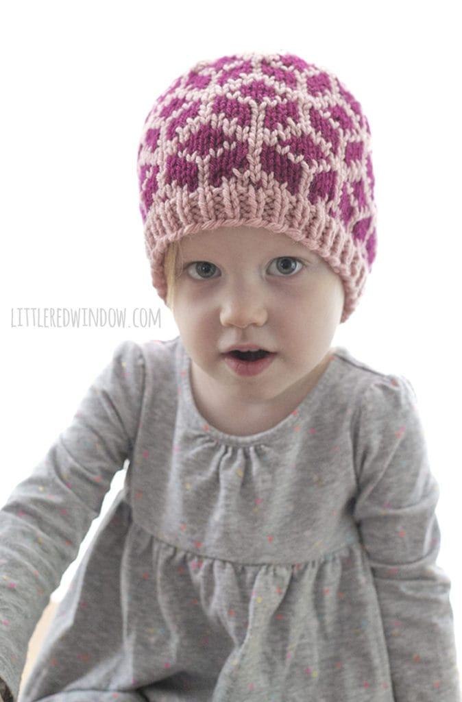 little girl wearing knit hat with tumbling blocks and looking surprised