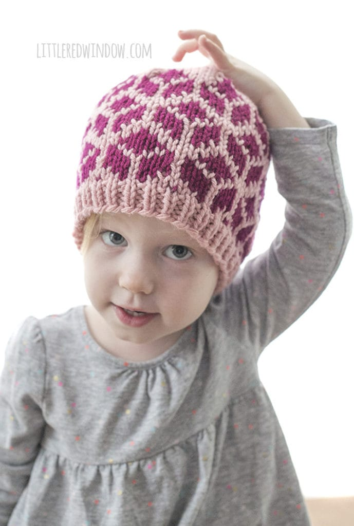 little girl wearing knit hat with tumbling blocks with one hand on top of her head
