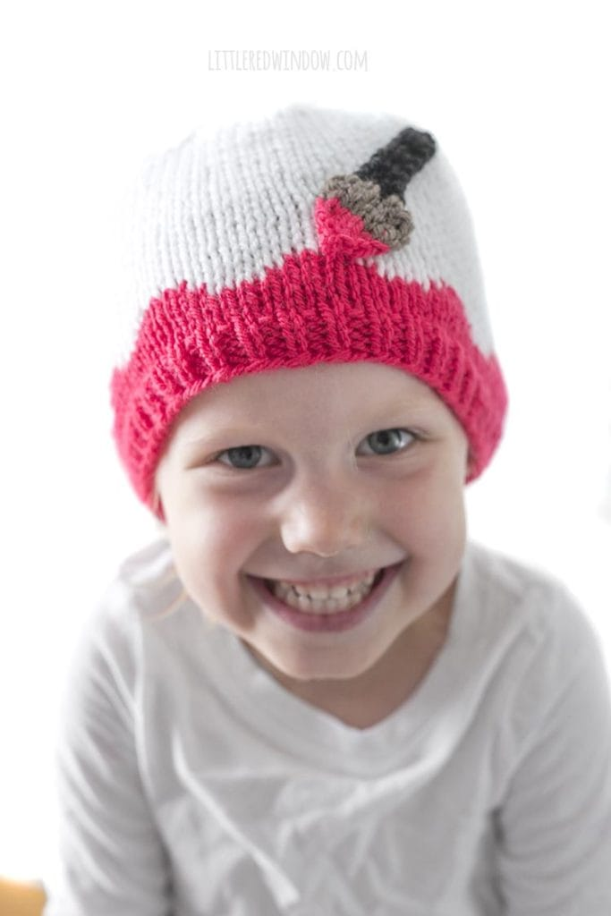 Little girl smiling big and wearing a white hat with pink along the brim and an applique paintbrush painting on the pink