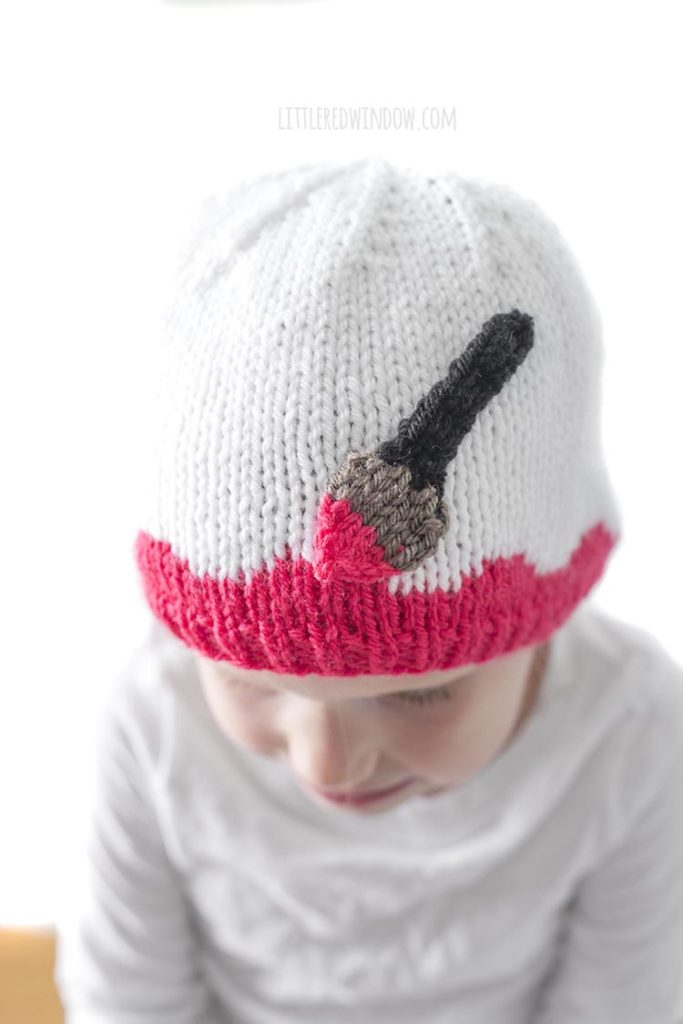 Little girl looking down and wearing a white hat with pink along the brim and an applique paintbrush painting on the pink
