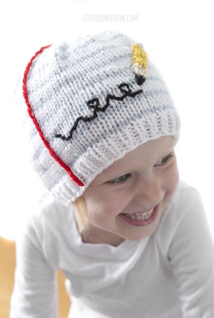 Little girl smiling and wearing a hat that looks like a piece of notebook paper with a pencil scribbling on it and looking to the right