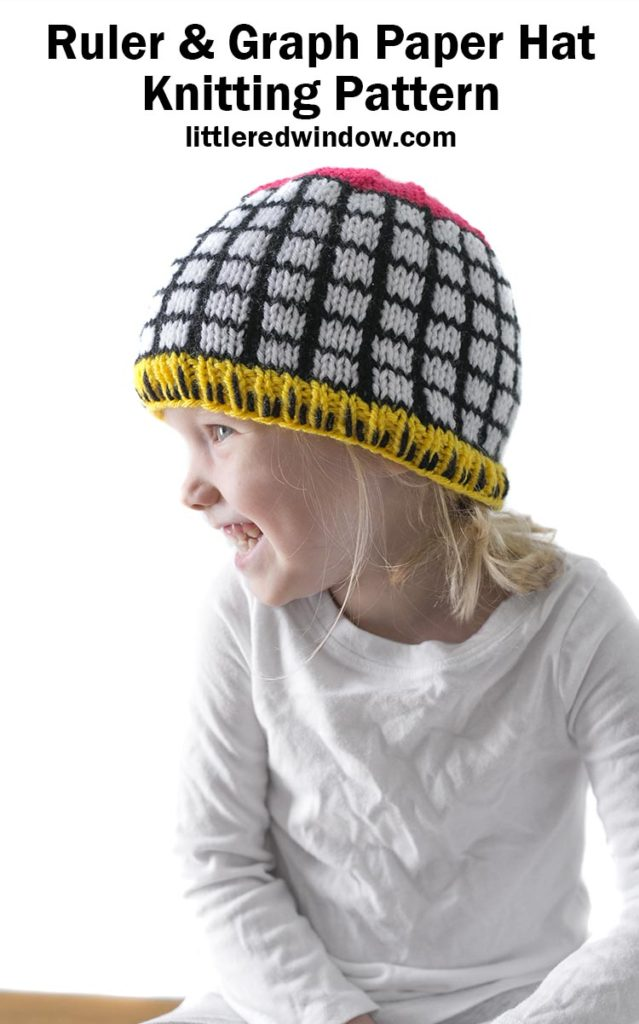 Little girl wearing black and white grid knit hat with yellow ruler brim and pink top looking to the left