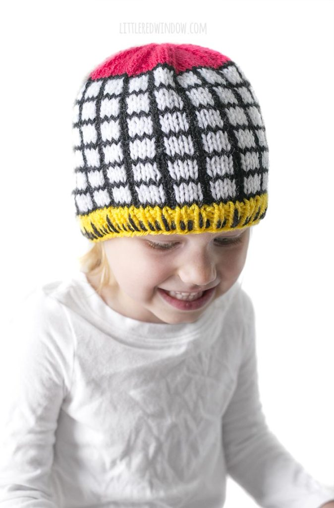Little girl wearing knit hat with black and white grid and yellow ruler brim