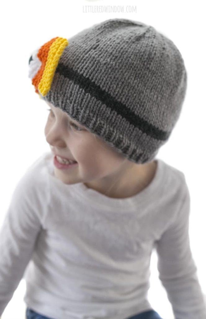 little girl in white shirt looking off to the left and wearing a gray knit hat with candy corn colored bow on the front