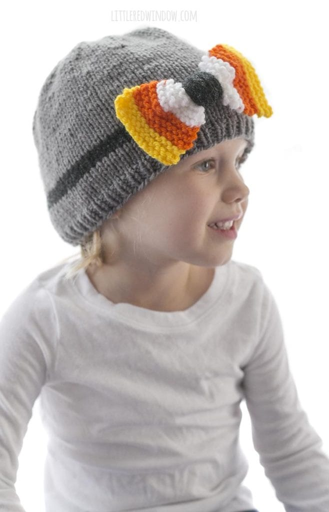 little girl in white shirt looking off to the right and wearing a gray knit hat with candy corn colored bow on the front
