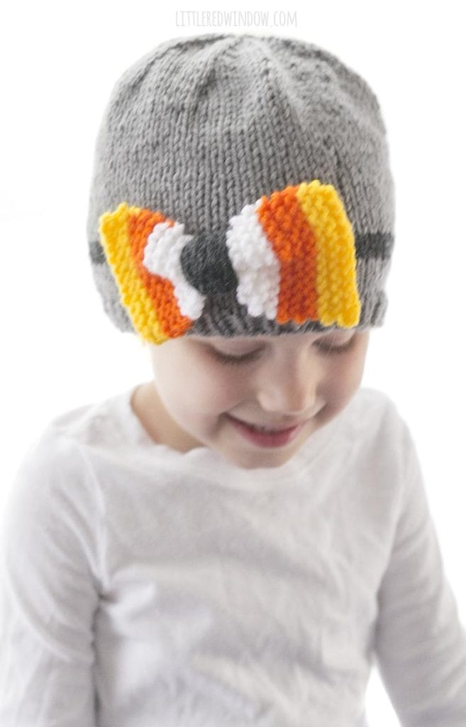 little girl looking down and wearing a gray knit hat with a bow striped yellow orange and white like candy corn