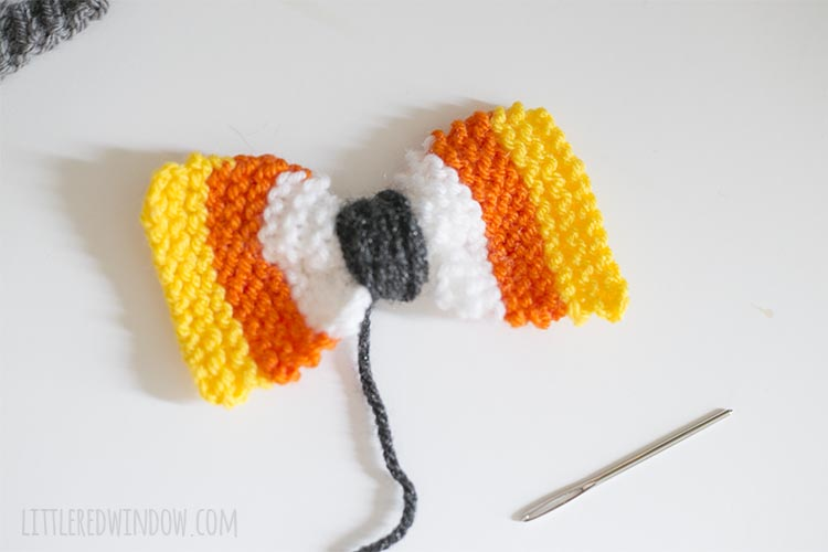 knit candy corn stripe rectangle with charcoal yarn wound around the center to make a bow