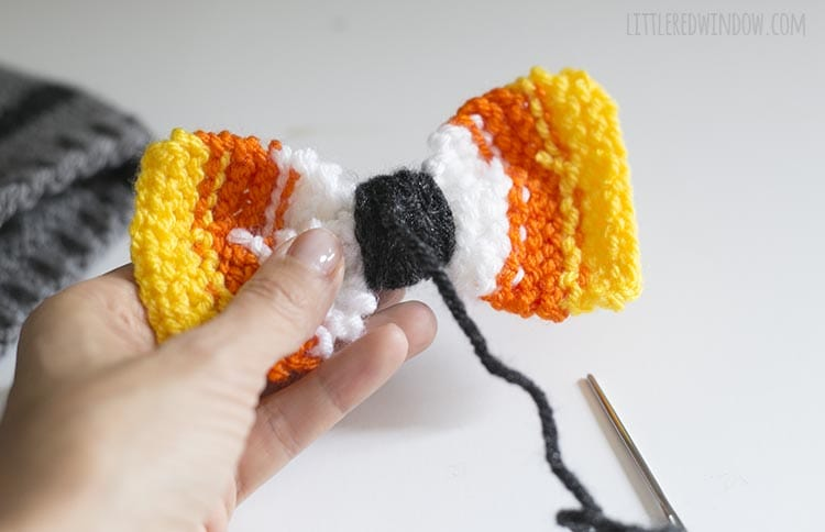hand holding bow backwards to show yarn knotted at the back of the bow