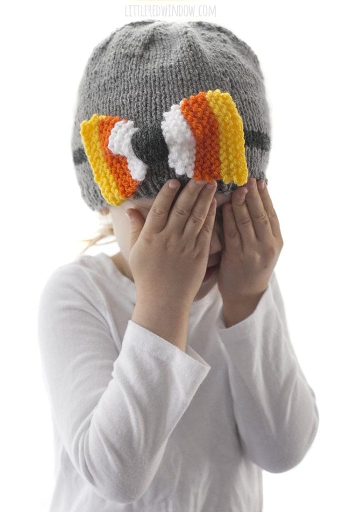 little girl with hands over face wearing a gray knit hat with candy corn colored bow on the front