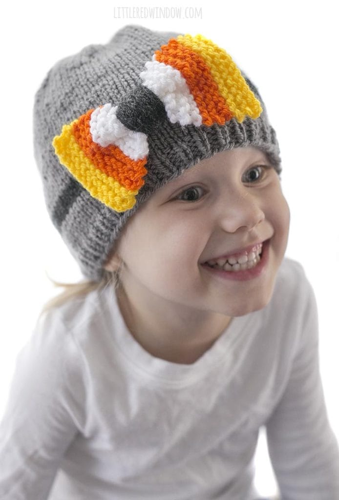 little girl in white shirt smiling and wearing a gray knit hat with candy corn colored bow on the front