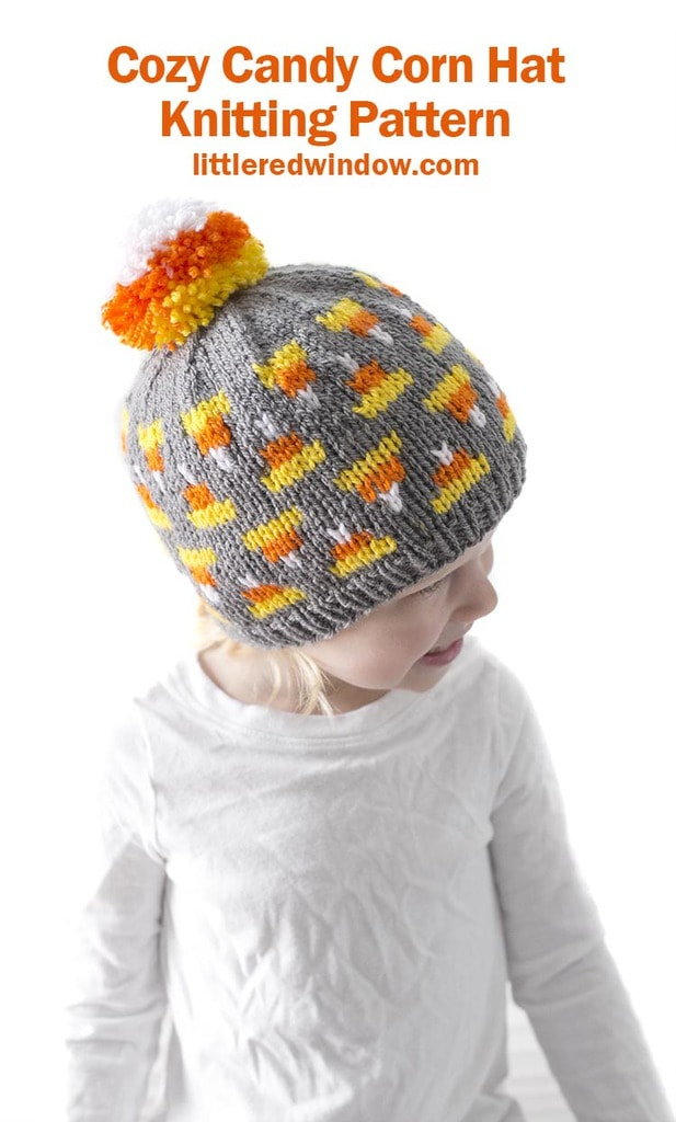 little girl in white shirt looking to the right and wearing gray knit hat with candy corn pattern on it and candy corn colored pom pom on top