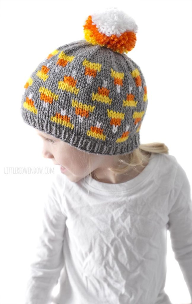 little girl in white shirt looking to the left and wearing gray knit hat with candy corn pattern on it and candy corn colored pom pom on top