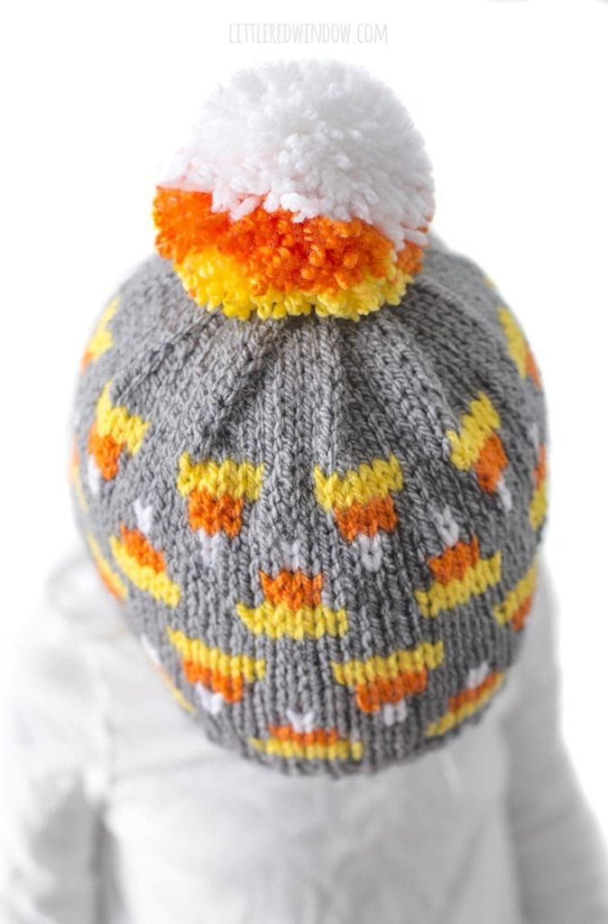 Closeup top view of round candy corn colored yarn pom pom on top of a gray knit baby hat with a fair isle candy corn pattern all over it