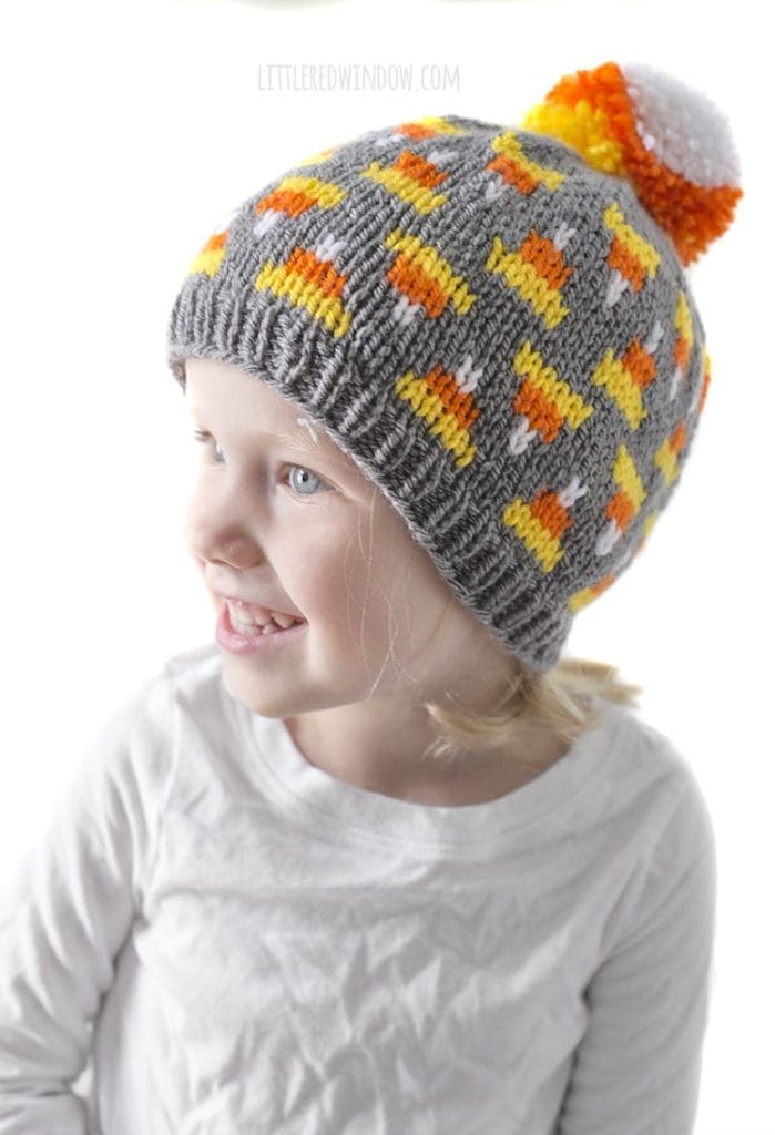 little girl in white shirt looking off to the left and wearing gray knit hat with candy corn pattern on it and candy corn colored pom pom on top