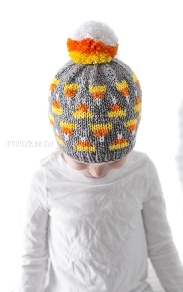 little girl in white shirt looking down and wearing gray knit hat with candy corn pattern on it and candy corn colored pom pom on top