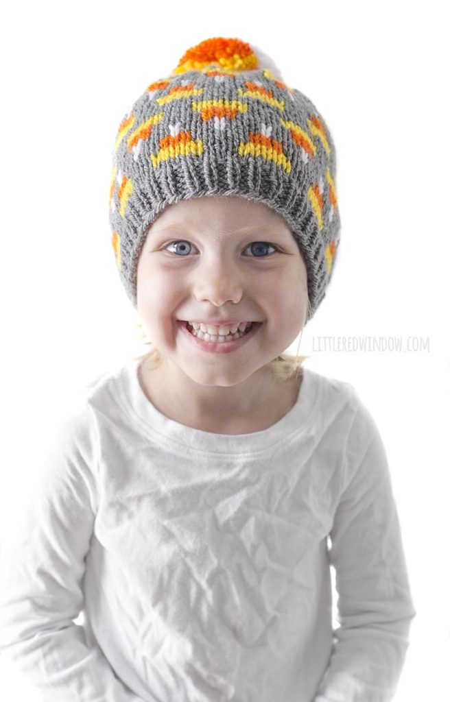 little girl in white shirt smiling and wearing gray knit hat with candy corn pattern on it and candy corn colored pom pom on top