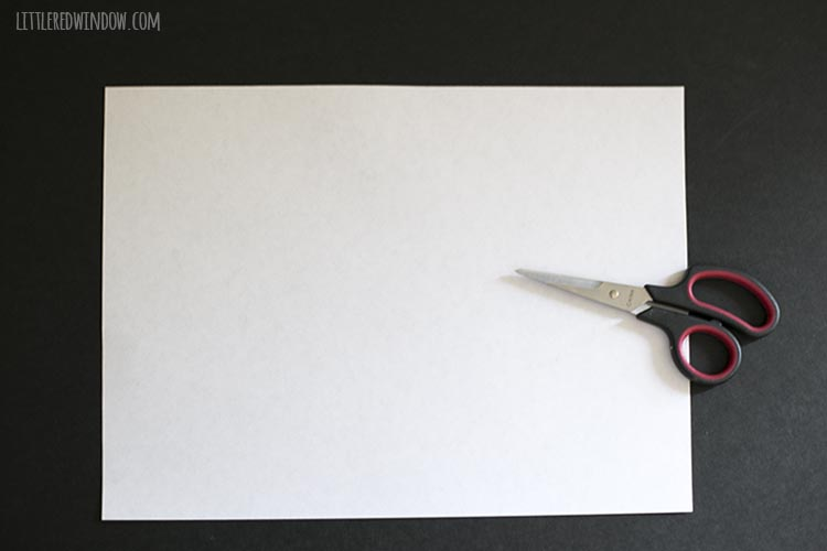 piece of letter size white paper and a pair of scissors on black background