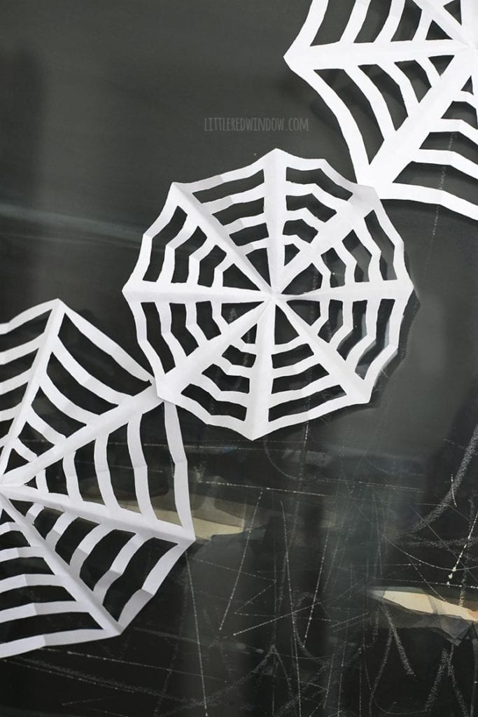 Closeup of three paper spiderwebs strung together on a wall