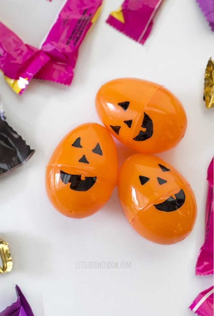 three orange easter eggs with jack o lantern faces on them