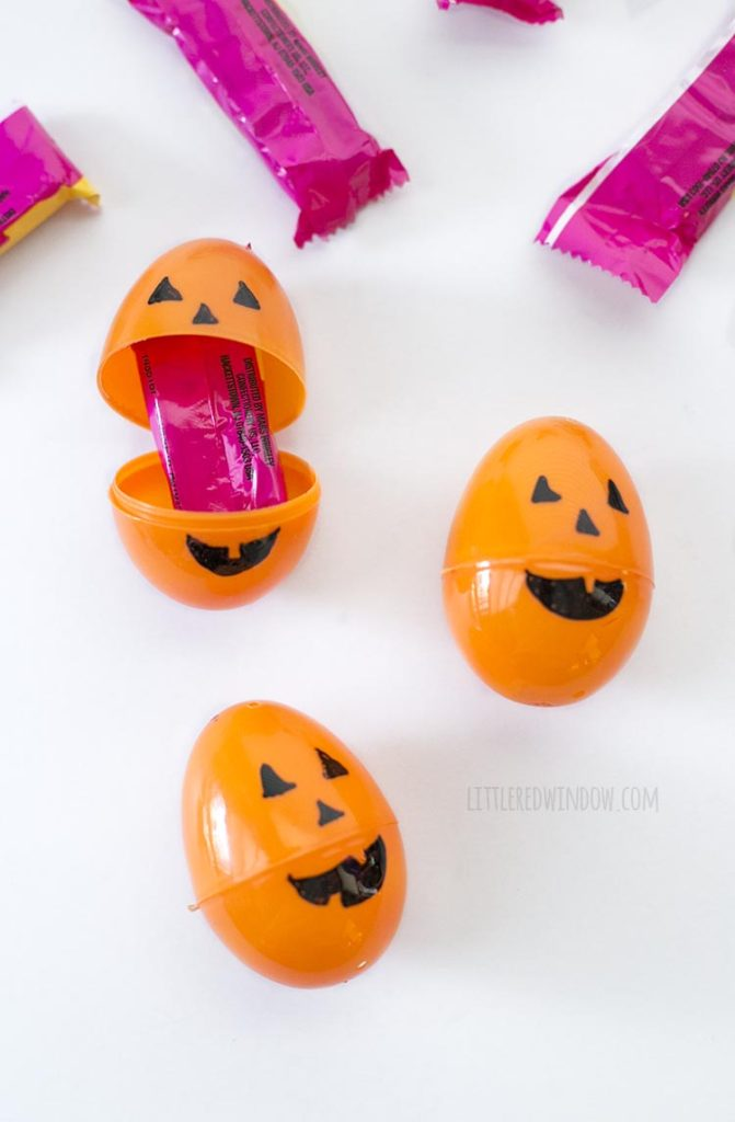 3 orange easter eggs with jack o lantern faces on them one open with candy inside