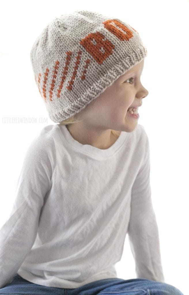 Little girl smiling and looking off to the right and wearing a tan knit hat with orange stripes and and the word BOO on the front