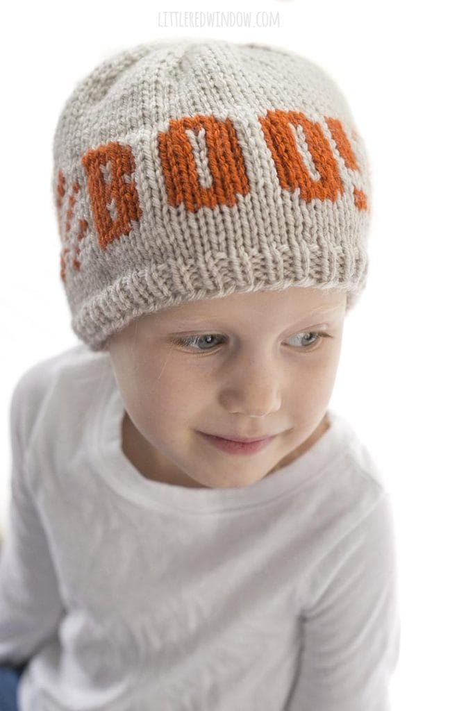 little girl looking down and wearing a tan and orange knit hat with the word BOO on the front