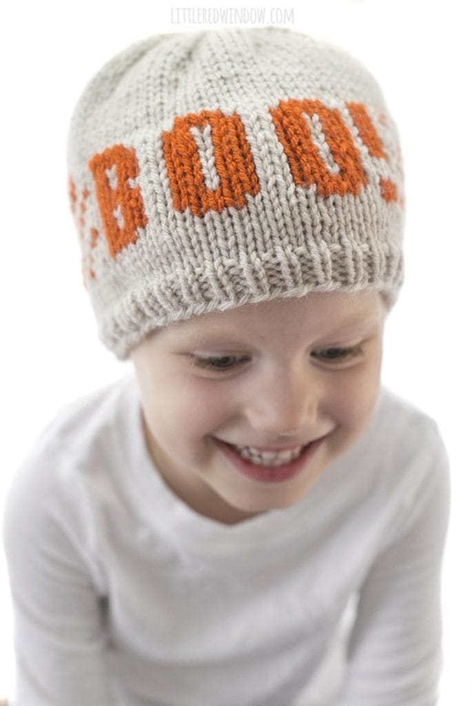 Top view of Little girl smiling and looking down and wearing a tan knit hat with orange stripes and and the word BOO on the front