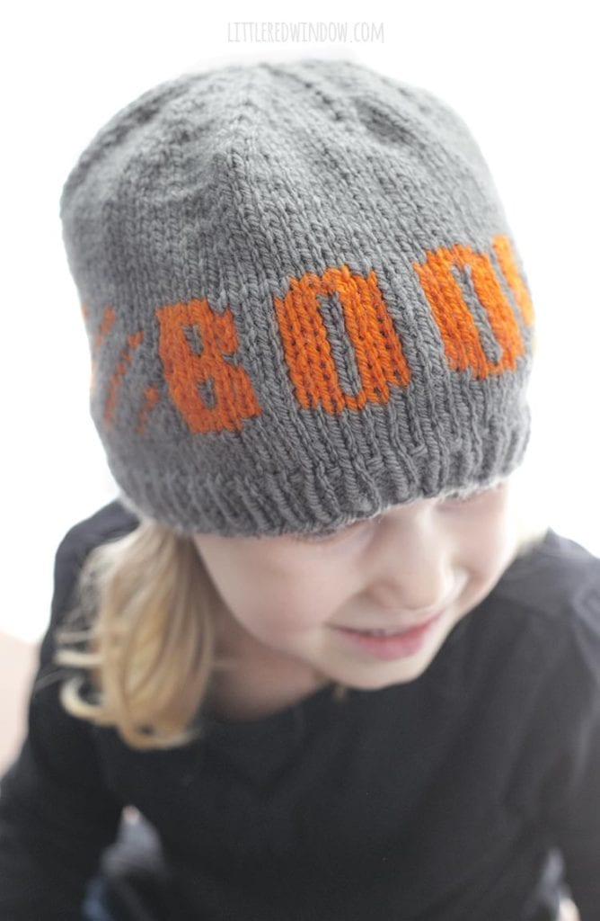 little girl looking down and wearing a gray knit hat with the word BOO on the front