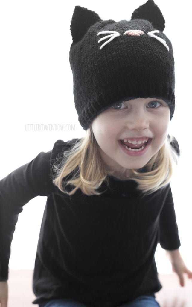 little girl laughing wearing a black shirt and knit black cat hat