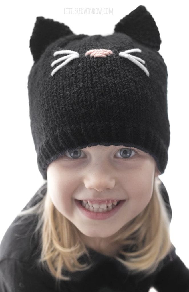 little girl looking up and smiling wearing a black shirt and knit black cat hat