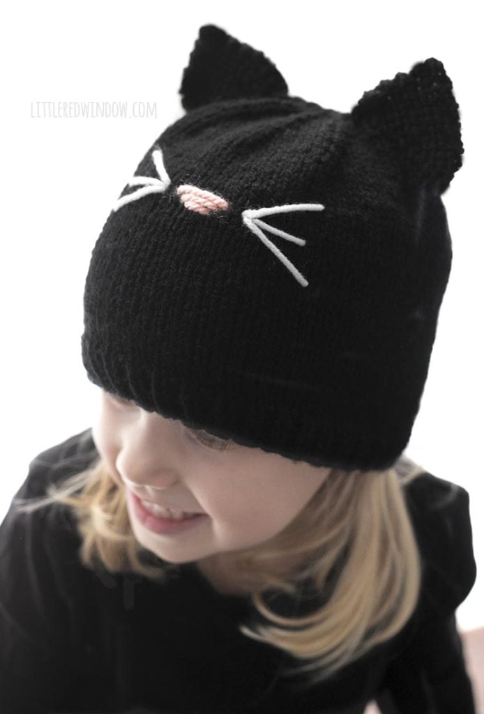 Little girl wearing black knit cat hat and looking off to the near left