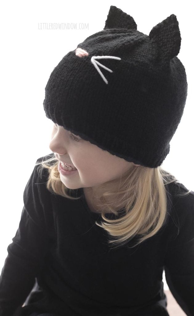 side view of little girl wearing black cat hat and looking off to the left