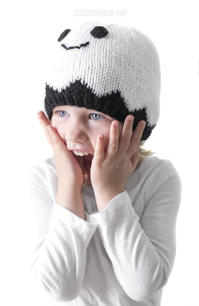 Little girl wearing white ghost hat with hands on cheeks making surprised face