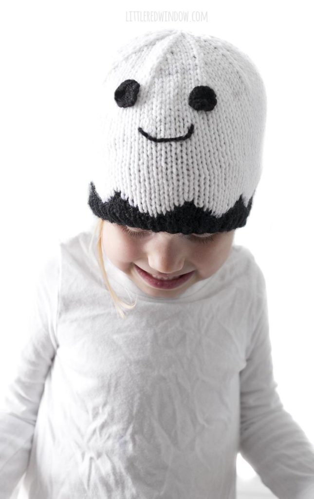 Little girl wearing smiling white ghost knit hat and looking down