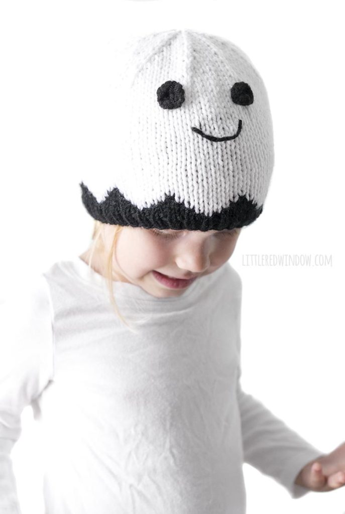 Little girl wearing smiling white ghost knit hat and looking down and to the right