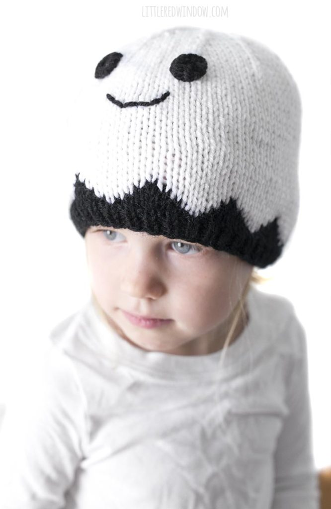 Little girl wearing a white smiling ghost hat and looking off to the left